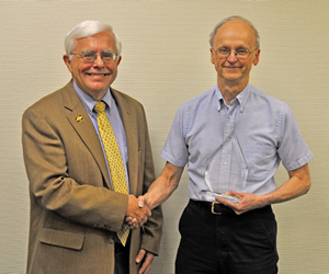 Dean Olson congratulates Frank Booth, PhD, on his Impact Award presented to member of the CVM faculty.