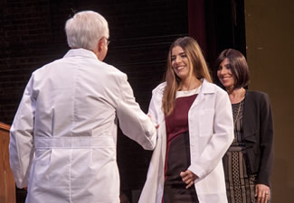 Dean Neil Olson congratulates Heidi Burgos after she is coated by her mother, Heidi Zayas.