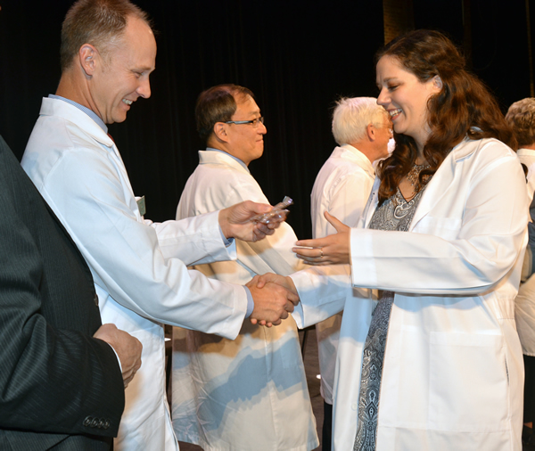 Cliff Miller, DVM, president of the Missouri Veterinary Medical Association, presents a name badge to Jaime Huff during the White Coat Ceremony for the CVM Class of 2019. The Missouri Veterinary Medical Foundation provided each third-year student with a name badge. The MVMA provided each student with a lapel pin for their white coat.