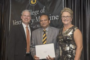Rajiv Mohan (center) received the 2018 Zoetis Award for Veterinary Research Excellence.  He is pictured with Nathan Voris of Zoetis and CVM Dean Carolyn Henry.
