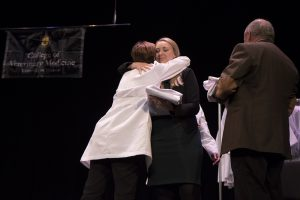 Associate Dean Angela Tennison presents a white coat to David Auxier's widow, Shannon, and his father, Doug.