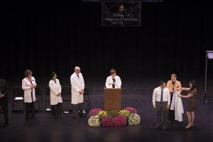 Amber Hegeman coats her husband, James, during the College of Veterinary Medicine's 18th Annual White Coat Ceremony.