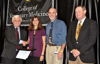 Elizabeth Bryda accepted the Zoetis Award for Veterinary Research Excellence from CVM Dean Neil C. Olson, last year's recipient Jeffrey Bryan, DVM, PhD, and Tom Kent of Zoetis.