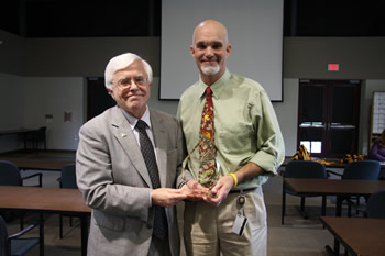 CVM Dean Neil C. Olson presents the Dean's Impact Award for faculty to Associate Professor Jeffrey Bryan.