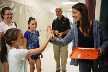 Associate Teaching Professor of Medical Oncology and Radiation Oncology Kim Selting, DVM, MS, DACVIM-Oncology, DACVR-Radiation Oncology, offers Emma Dean a high-five after she and her sister presented the money they raised for research into canine osteosarcoma.