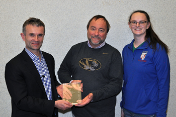 B. Duncan Lascelles receives a plaque in appreciation for his lectures at the CVM from Philip Johnson, professor of equine medicine, and second-year student Crystal Climer, president of the Student Chapter of the American Veterinary Medical Association at Mizzou.