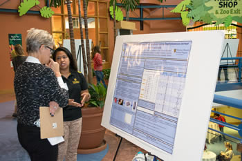 Geraline Arroyo discusses her research with an attendee at the WAMCOH inaugural One Health Conference.