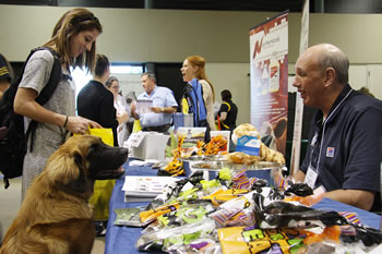 Hill's Pet Nutrition representative Dave Rosen talks to second-year veterinary student Abby Romano as her dog, Rooney, eyes some of the treats Rosen has available at his table during the CVM Veterinary Products Night.