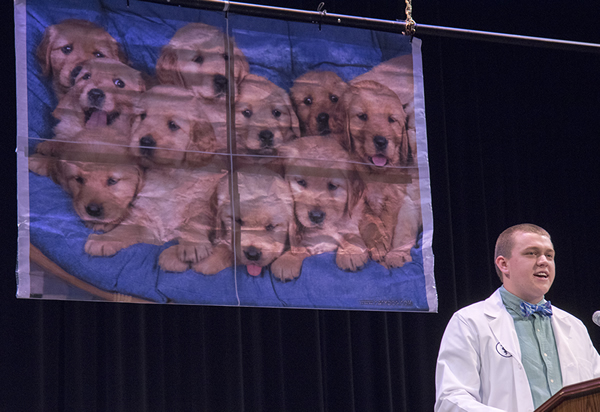 Class of 2019 President Tanner May offered a response on behalf of his peers using a photo of puppies that had cheered the class through times of stress as a backdrop.