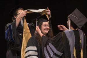 Associate Deans Linda Berent (left) and Angela Tennison hood Rebecca Cooper.