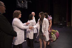 Cindy Penrod, DVM, president of the Missouri Veterinary Medical Association, presents a lapel pin to Kelly Bosco.