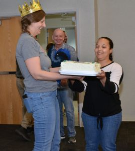 Armedia O'Neill presents Shelly Nail with a cake she made to celebrate Nail's selection as this year's recipient of the University of Missouri's Chancellor's Outstanding Staff Award as her nominator Craig Franklin looks on.
