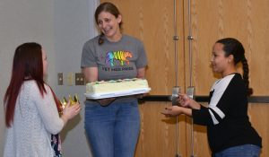 Shelly Nail receives a crown and a cake from colleagues Sammy Gerb (left) and Armedia O'Neill.
