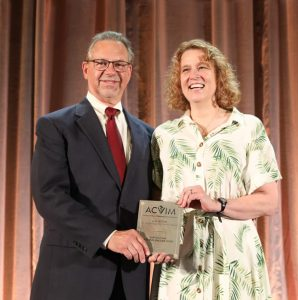 Leah Cohn receives the Lee and Inge Pyle Service Award from Allen Roussel, DVM, MS, DACVIM a professor and department head at Texas A&M College of Veterinary Medicine, and one of the colleagues who wrote letters supporting Cohn's nomination.
