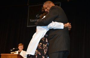 Proud father Garland Hughes hugged his daughter, Danielle Hughes, after presenting her white coat.