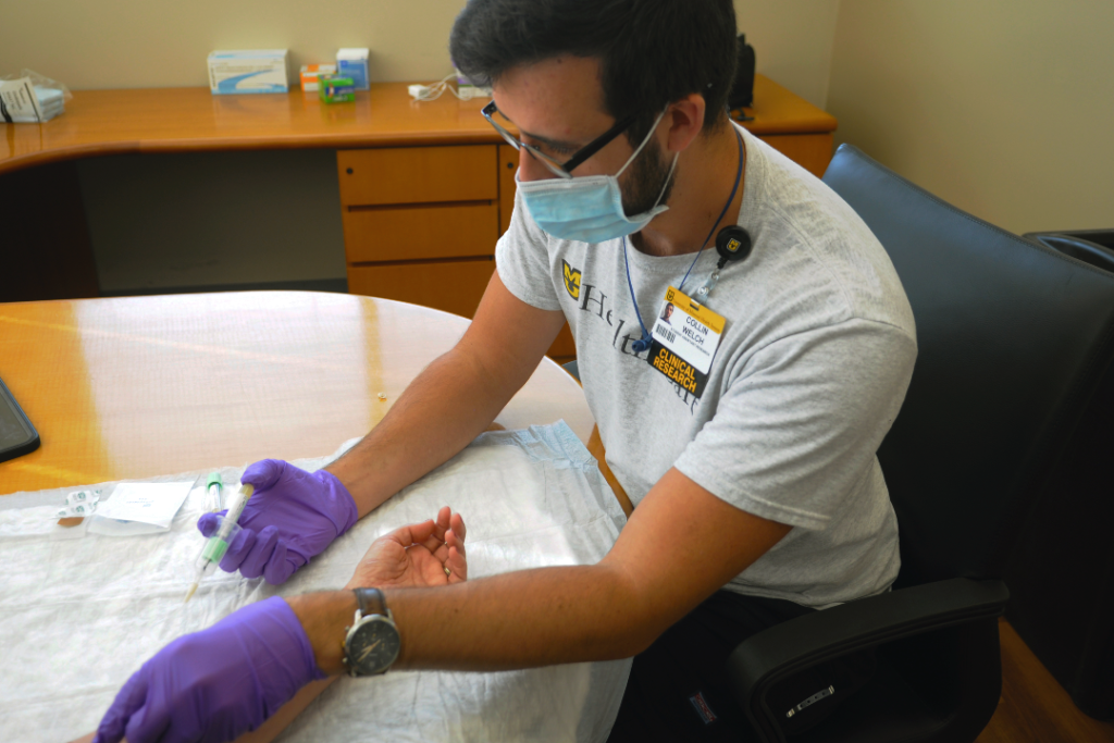 A member of the research team draws a blood sample from a participant.
